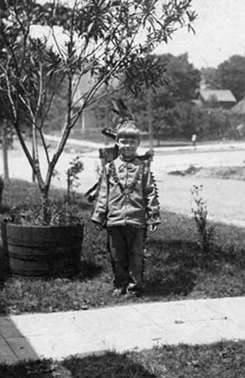 An American child of unknown ethnic origin, living in a state where trees grow in barrels, around 1910, wearing an Indian costume.